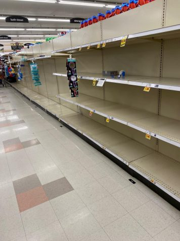 Empty shelves in the King Soopers aisle dedicated to toilet paper and paper towels.