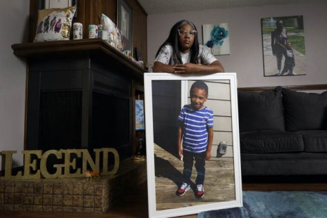Charron Powell stands with a photo of her son, LeGend Talieferro, at her home in Raytown, Mo. on Sunday, Oct. 3, 2021. LeGend was 4 years old when he was fatally shot June 29, 2020 while he was sleeping in an apartment staying with his father.